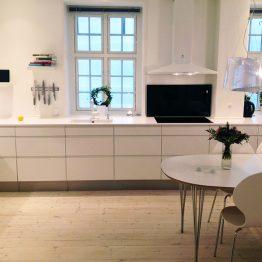 Aubo køkken Ringsted, hvidt køkken med bord og stol i midten